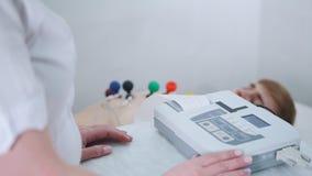 Μια ιατρική κλινική Ένα άτομο που λαμβάνει μια διαδικασία ECG Μια ταινία αποτελεσμάτων που βγαίνει από τη μηχανή απόθεμα βίντεο