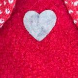Μια καρδιά που ράβεται σε ένα κόκκινο μάλλινο πουλόβερ στοκ εικόνες