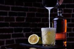 Μια κλασική συνταγή για το ουίσκυ ξινό - το μπέρμπον, το σιρόπι καλάμων και το χυμό λεμονιών, που διακοσμούνται με με το πορτοκάλ στοκ φωτογραφία