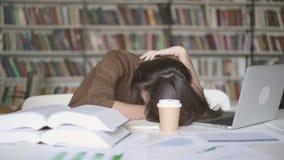 Μια κουρασμένη πτώση ανδρών σπουδαστών κοιμισμένη στη βιβλιοθήκη απόθεμα βίντεο