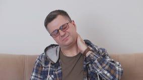 Μια μέσης ηλικίας συνεδρίαση ατόμων σε έναν καναπέ θα δοκιμάσει τον πόνο στην αυχενική περιοχή και συμπλέκτης το χέρι του από το  φιλμ μικρού μήκους