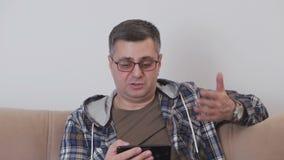 Μια μέση ηλικίας συνεδρίαση ατόμων σε έναν καναπέ που χρησιμοποιεί το βίντεο που καλεί μέσα ένα smartphone επικοινωνεί με το άλλο απόθεμα βίντεο