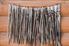 Μια μεγάλη ομάδα παλαιών οβελιδίων μετάλλων για το κρέας είναι σε ένα καλώδιο σε δύο καρφιά σε ένα πορτοκαλί ξύλινο υπόβαθρο τοίχ στοκ εικόνες