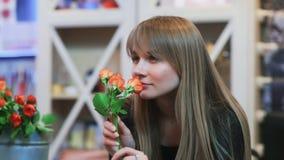Μια νέα γυναίκα που μυρίζει ένα λουλούδι σε ένα κατάστημα απόθεμα βίντεο