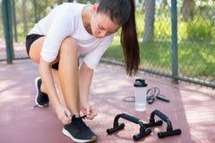 Μια νέα κατάλληλη γυναίκα που παίρνει έτοιμη να ασκήσει στο πάρκο στοκ εικόνες με δικαίωμα ελεύθερης χρήσης