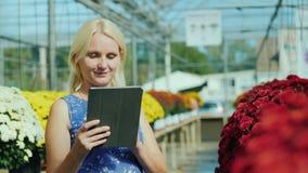 Μια νέα καυκάσια γυναίκα χρησιμοποιεί μια ψηφιακή ταμπλέτα Εργασίες στο βρεφικό σταθμό των λουλουδιών φιλμ μικρού μήκους