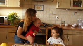 Μια νέα νοικοκυρά με ένα μωρό στα όπλα της ταΐζει μια προσχολική κόρη Mom με δύο παιδιά το λουλούδι ημέρας δίνει το γιο μητέρων m φιλμ μικρού μήκους