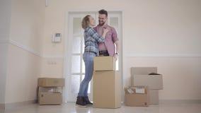 Μια νεολαία συνδέει την κίνηση σε ένα νέο σπίτι Ένα ζεύγος στέκεται στο κατώφλι δίπλα στα κιβώτια και το αγκάλιασμα Οικογένεια απόθεμα βίντεο