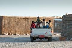 Μια ομάδα παιδιών στο πίσω μέρος ενός γύρου ανοιχτών φορτηγών μέσω ενός βεδουίνου χωριού στη Χερσόνησο του Σινά στοκ εικόνες