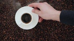Μια δέσμη του χεριού φασολιών καφέ προσεκτικά βάζει ένα φλυτζάνι του αρωματικού καφέ με Crema και καπνώδης απόθεμα βίντεο