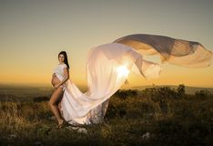 Μια όμορφη έγκυος λευκιά ντυμένη γυναίκα που στέκεται στο ηλιοβασίλεμα στοκ φωτογραφίες