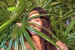 Μια όμορφη γυναίκα κρύβει πίσω από τα φύλλα φοινικών Ανατολική φροντίδα ομορφιάς και δέρματος στοκ φωτογραφίες με δικαίωμα ελεύθερης χρήσης