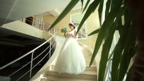 Μια όμορφη νύφη σε ένα φόρεμα δαντελλών στέκεται στα μεγάλα βήματα απόθεμα βίντεο