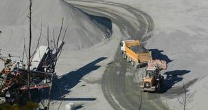 Μια σύγχρονη εργασία εκσακαφέων σε μια σταδιοδρομία, ένας πορτοκαλής εκσακαφέας φορτώνει τις πέτρες σε ένα φορτηγό απορρίψεων απόθεμα βίντεο