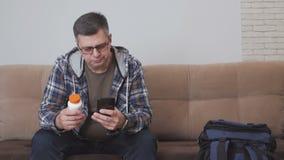 Μια συνεδρίαση ατόμων σε έναν καναπέ κρατά ένα βάζο των χαπιών στα χέρια του και χρησιμοποιεί ένα κινητό τηλέφωνο Εδώ κοντά είναι απόθεμα βίντεο