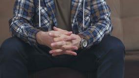 Μια συνεδρίαση ατόμων στον καναπέ gesticulates με τα χέρια του, ζαρώνει τους και τα τριψίματα ο ένας εναντίον του άλλου απόθεμα βίντεο