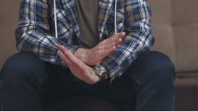 Μια συνεδρίαση ατόμων στον καναπέ gesticulates με τα χέρια του, που διασχίζουν τις παλάμες του απόθεμα βίντεο