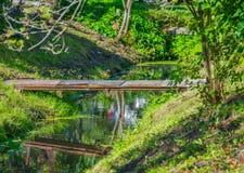 Μια τραχιά σπιτική ξύλινη γέφυρα πέρα από μια τάφρο στο χωριό διακοπών στοκ φωτογραφία