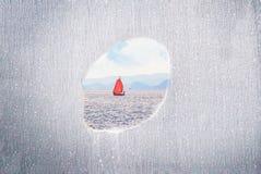 Μια τρύπα σε έναν τοίχο με την πλέοντας βάρκα στην ήρεμη θάλασσα Περιορισμένη έννοια περιοχή, ελευθερία διάστημα αντιγράφων στοκ εικόνα με δικαίωμα ελεύθερης χρήσης