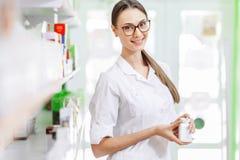 Μια χαμογελώντας γοητευτική λεπτή σκοτεινός-μαλλιαρή κυρία με τα γυαλιά, που φορούν ένα άσπρο παλτό, στέκεται δίπλα στο ράφι και  στοκ εικόνα με δικαίωμα ελεύθερης χρήσης