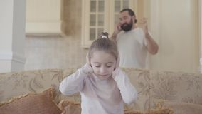 Μικρή συνεδρίαση κοριτσιών πορτρέτου στον καναπέ και κάλυψη των αυτιών της επειδή ο μπαμπάς της μιλά δυνατά στο τηλέφωνο απόθεμα βίντεο