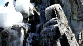 Μικρός καταρράκτης στο χιονισμένο βράχο