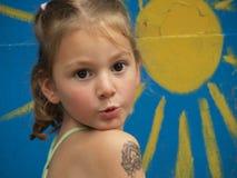 Μικρό κορίτσι με μια δερματοστιξία των παιδιών στο αντιβράχιό της στο υπόβαθρο του χρωματισμένου ήλιου στοκ εικόνα