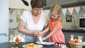 Μικρό κορίτσι με το grandma που βάζει την κρέμα στα μπισκότα απόθεμα βίντεο