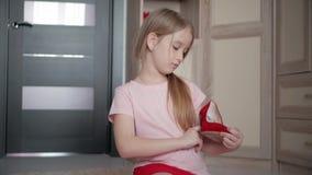 Μικρό κορίτσι στο πάτωμα που δοκιμάζει στο σπίτι mom τα κόκκινα υψηλά παπούτσια τακουνιών φιλμ μικρού μήκους