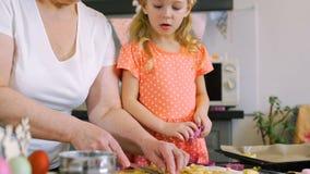 Μικρό κορίτσι που κόβει τα μπισκότα Πάσχας με το grandma απόθεμα βίντεο