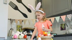 Μικρό κορίτσι που διακοσμεί τα μπισκότα και που δοκιμάζει την κρέμα απόθεμα βίντεο