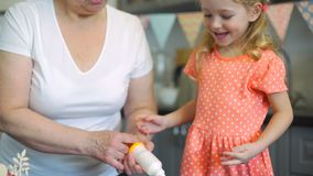 Μικρό κορίτσι που διακοσμεί τα μπισκότα με τη γιαγιά φιλμ μικρού μήκους