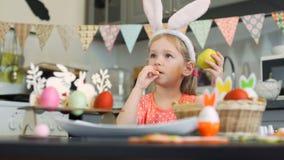 Μικρό κορίτσι που τρώει τα μπισκότα και το μήλο σε Πάσχα απόθεμα βίντεο