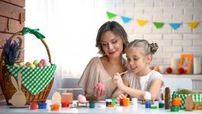 Μικρό κορίτσι που προσπαθεί να χρωματίσει το αυγό Πάσχας, το βοηθώντας και ενισχυτικό παιδί αγαπώντας μητέρων στοκ εικόνα με δικαίωμα ελεύθερης χρήσης