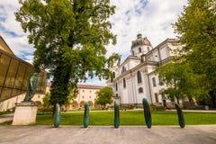 Μικρό πάρκο Furtwaenglerpark κοντά στο πανεπιστήμιο του Σάλτζμπουργκ και συλλογική εκκλησία Kollegienkirche στην παλαιά πόλη του  στοκ φωτογραφία με δικαίωμα ελεύθερης χρήσης