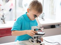 Μικρό παιδί που κάνει την έρευνα βιοχημείας στο εργαστήριο Ένα αγόρι της ευρωπαϊκής εμφάνισης σε ένα πόλο πραγματοποιεί τα βιολογ στοκ εικόνες
