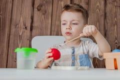 Μικρό παιδί που χρωματίζει τα ζωηρόχρωμα αυγά για Πάσχα στο ξύλινο υπόβαθρο ελεύθερη απεικόνιση δικαιώματος
