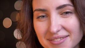 Μισό-πορτρέτο κινηματογραφήσεων σε πρώτο πλάνο στο σχεδιάγραμμα της νέας καυκάσιας προσοχής κοριτσιών με το ήρεμο χαμόγελο στη κά απόθεμα βίντεο