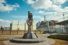 Μνημείο στους εκκαθαριστές του Τσέρνομπιλ και τέταρτος αντιδραστήρας χωρίς να εσωκλείσει τη Σαρκοφάγο Πυρηνικός σταθμός Chornobyl στοκ φωτογραφία με δικαίωμα ελεύθερης χρήσης