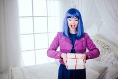Μοντέρνος φρικτός Η γοητεία εξέπληξε την όμορφη γυναίκα με την μπλε τρίχα κρατά το δώρο στην άσπρη κρεβατοκάμαρα Μόδα και στοκ φωτογραφία