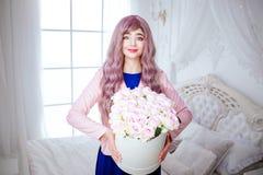 Μοντέρνος φρικτός Η γοητεία που χαμογελά την όμορφη γυναίκα με τη μακριά ιώδη τρίχα κρατά το άσπρο κιβώτιο με τα λουλούδια στεμέν στοκ εικόνα με δικαίωμα ελεύθερης χρήσης