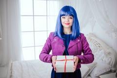 Μοντέρνος φρικτός Το πορτρέτο της γοητείας που χαμογελά την όμορφη γυναίκα με την μπλε τρίχα κρατά το δώρο στην άσπρη κρεβατοκάμα στοκ φωτογραφίες