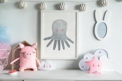 Μοντέρνο Σκανδιναβικό νεογέννητο ράφι μωρών με τη χλεύη επάνω στο πλαίσιο φωτογραφιών, το κιβώτιο, τη teddy αρκούδα και τα παιχνί στοκ εικόνες