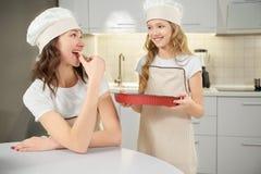 Μορφή ψησίματος εκμετάλλευσης κορών, δοκιμάζοντας μπισκότο μητέρων στοκ εικόνα με δικαίωμα ελεύθερης χρήσης