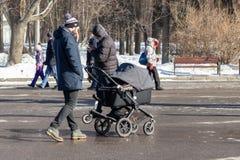 ΜΟΣΧΑ, ΡΩΣΙΑ - 2 ΜΑΡΤΊΟΥ 2019: Ενιαίο άτομο με τον περιπατητή μωρών, περίπατοι μεταφορών στο χειμερινό πάρκο στοκ εικόνα με δικαίωμα ελεύθερης χρήσης