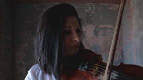 Μουσικός γυναικών στο άσπρο πουκάμισο που παίζει το βιολί απόθεμα βίντεο