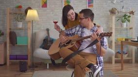 Μουσικός νεαρών άνδρων με τα γυαλιά που παίζει την κιθάρα προσεγγίζεται από μια νέα γυναίκα με ένα ποτήρι του κρασιού απόθεμα βίντεο