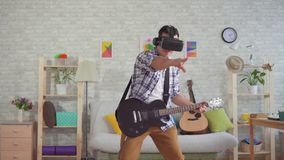 Μουσικός νεαρών άνδρων πορτρέτου στα γυαλιά VR που παίζουν συναισθηματικά την ηλεκτρική κιθάρα απόθεμα βίντεο