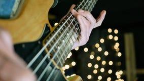 Μουσικός που παίζει την ηλεκτρική κιθάρα στο υπόβαθρο αστεριών θαμπάδων φιλμ μικρού μήκους