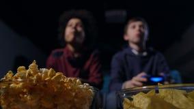 Μουτζουρωμένα gamers εφήβων που τρώνε popcorn και που παίζουν το παιχνίδι απόθεμα βίντεο